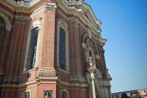 Fassade des Michels mit Turm im Hintergrund und Pfarrer im Vordergrund